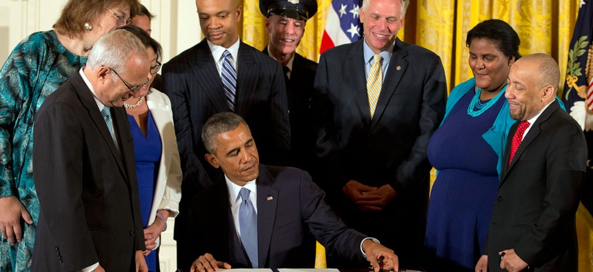 Surrounded by LGBT supporters, President Barack Obama signs executive orders to protect LGBT employees from federal workplace discrimination.