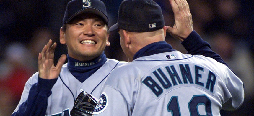 Seattle Mariners relief pitcher Kazuhiro Sasaki celebrates with right fielder Jay Buhner after defeating the New York Yankees.