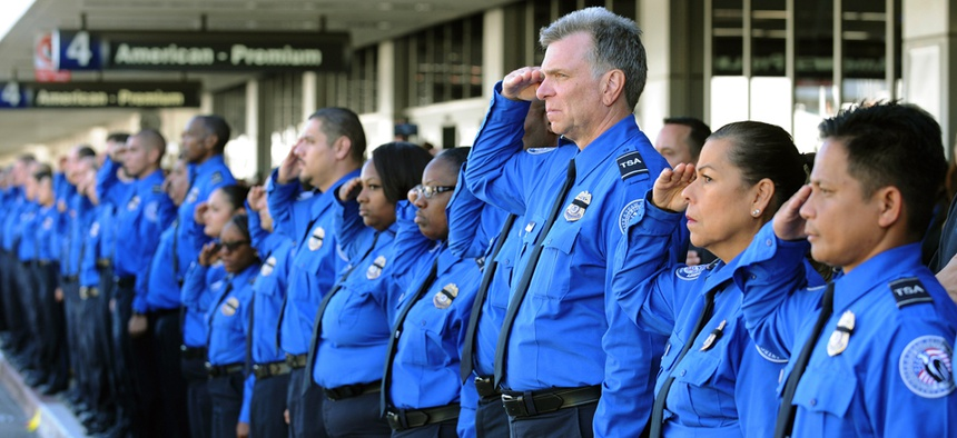 long line of Transportation Security Administration personnel salute as the Honor Flag leaves Los Angeles international airport after a TSA agent was shot there in November.