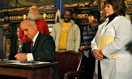 Minnesota Gov. Mark Dayton signs two executive orders implementing early Medicaid enrollment as his official first act as governor.
