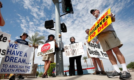 John Zemblidge, right, of Phoenix, leads a group of about a dozen death penalty opponents in prayer as they protest the execution of Joseph Wood at the state prison in Florence, Ariz.