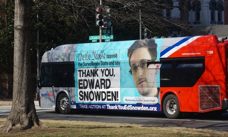 A bus in DC is affixed with an ad supporting Edward Snowden in March.