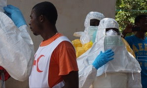 Health workers put on protective gear in Sierra Leone in 2013.