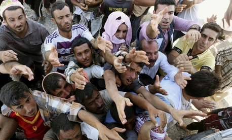 Displaced Iraqis from the Yazidi community gather for humanitarian aid Aug. 10.