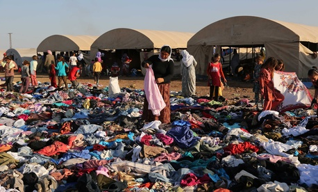 Displaced Iraqis from the Yazidi community look for clothes to wear among items provided by a charity organization at the Nowruz camp in Syria.