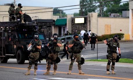 Police in riot gear work near crowds gathering in Ferguson Monday evening.