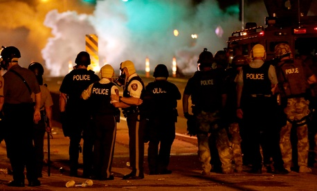 Police talk after deploying tear gas Sunday evening in Ferguson, Missouri.