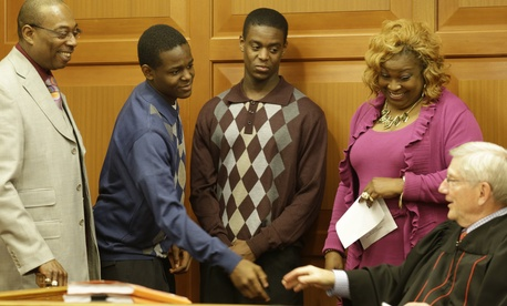 Jamal Byers, left center, shakes hands with Judge James Cissell, right, after Jamal and Tyshawn Byers, right center, were adopted by the Rev. Edward Byers, left, and his wife Darnette Byers, last November in Cincinnati. Adoption is a desired outcome for m