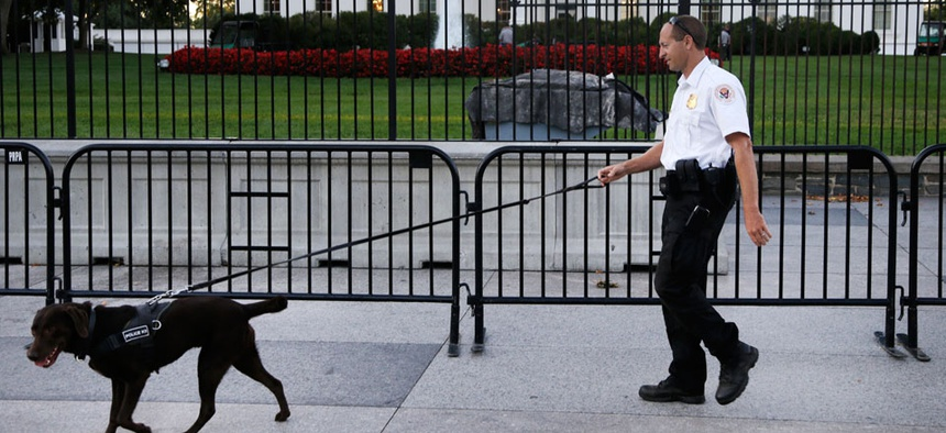 A member of the Secret Service Uniformed Division with a K-9 walks along the perimeter fence on Sept. 22.