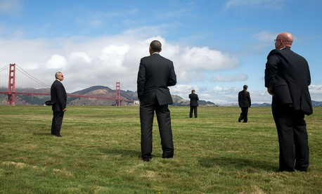 President Obama  stands with U.S. Secret Service agents and looks at the Golden Gate Bridge, prior to boarding Marine One at the Crissy Field landing zone for departure from San Francisco on July 23, 2014.