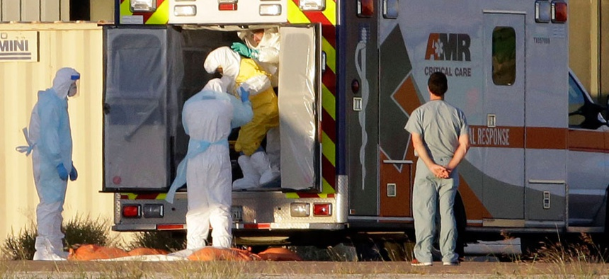 Medical staff in protective gear escort Nina Pham to a plane at Dallas' Love Field.
