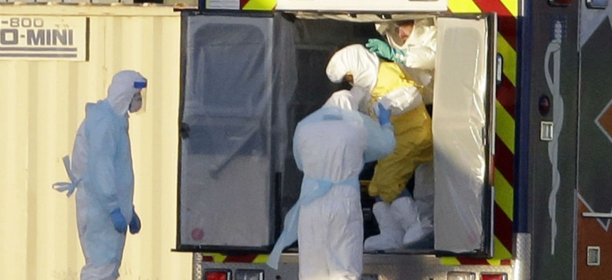 Medical personnel escort Nina Pham, one of the nurses who contracted Ebola in Dallas, to an aircraft.