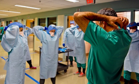 Navy Cmdr. James Lawler, right, a member of the Defense Department medical support team, shows students how to remove their personal protective equipment during training in San Antonio last week.