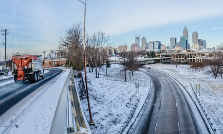 In this file photo, a snow plow at left treats a highway overpass near Charlotte's Uptown central business district.