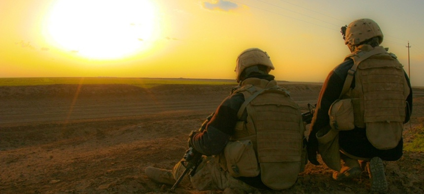 U.S. Marines take a break to watch the sunset after a dismounted patrol in Iraq in 2009.
