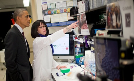 President Obama listens to Dr. Nancy Sullivan, chief of biodefense research at the National Institute of Allergy and Infectious Diseases, during an NIH tour.