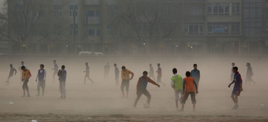 Afghan boys play football in the city of Kabul, Afghanistan, Monday, Dec. 29, 2014.