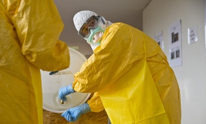 A licensed clinician sanitizes his hands after a simulated training session on Ebola given by CDC in October.