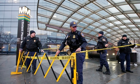 Metro Transit Police  officers secure the entrance to L'Enfant Plaza Metro station Monday.