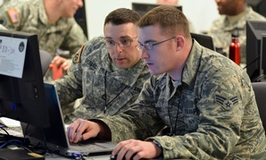 Army Sgt. 1st Class Michael Deblock, Vermont Army National Guard Computer Network Defense Team, left, discusses new ways to make the exercise more challenging for cyber defenders with a fellow Red Cell team member during the 2014 Cyber Shield exercise.