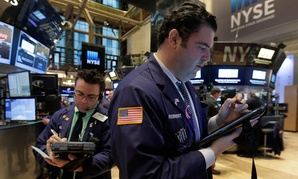 Trader Robert McQuade, right, works on the floor of the New York Stock Exchange, Thursday, March 5, 2015.