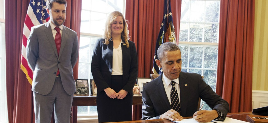 Obama signs the executive order, as Senior Adviser Brian Deese and Federal Chief Sustainability Officer Kate Brandt look on.