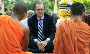 David Ensor, center, director of the Voice of America, listens to Cambodian Buddhist monks near Phnom Penh, Cambodia, in 2012.