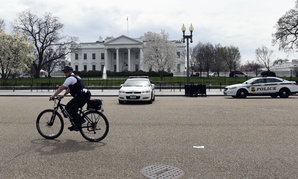 A Secret Service agent rides his bike by the White House on April 7 during widespread power outages across Washington.