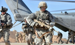 A U.S. Army soldier of the 2nd Battalion, 504th Parachute Infantry Regiment, 1st Brigade Combat Team, 82nd Airborne Division runs over to provide security after unloading from a CH-53 Sea Stallion helicopter.