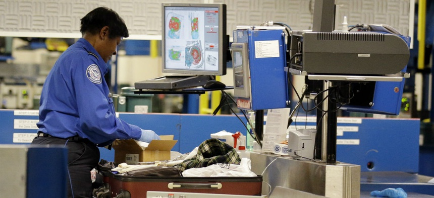 A TSA screener checks bags at Chicago's Midway International Airport during the 2014 holiday season.