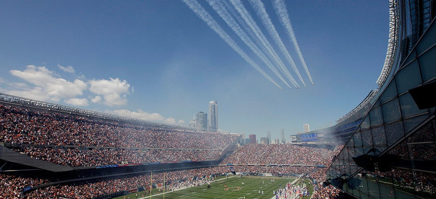 Military planes participate in a flyover at Soldier Field in September.