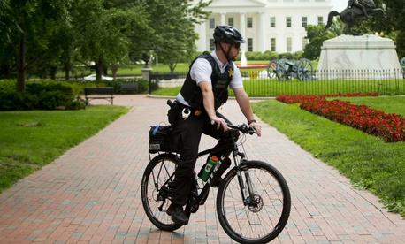 A Secret Service officer patrols Lafayette Park across from the White House on Tuesday.