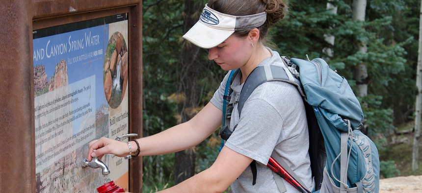 A hiker fills up her bottle at a water station at Grand Canyon National Park in 2013.