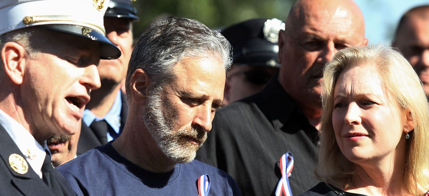 Jon Stewart and Sen. Kirsten Gillibrand stand with New York City first responders during a rally on Capitol Hill
