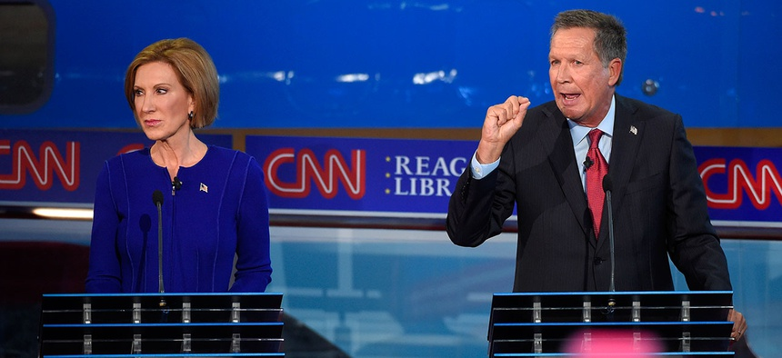 Carly Fiorina, left, looks on as John Kasich speaks during the CNN Republican presidential debate at the Ronald Reagan Presidential Library and Museum, Wednesday, Sept. 16.