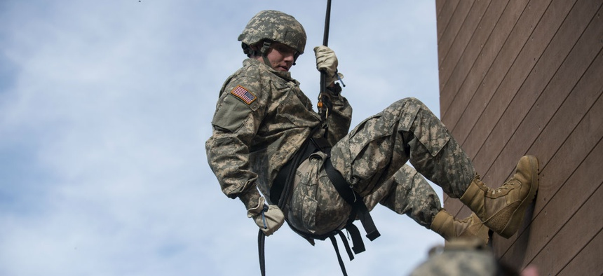 A U.S. Army Reserve military police soldier rappels down a 40-foot tower during training at Camp Atterbury, Ind.