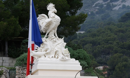 A French flag flies at half-mast by a symbol for France, the Gallic rooster, on the top of a war memorial in a cemetery in tribute to the victims of last Friday's attacks in Paris, in Beausoleil.