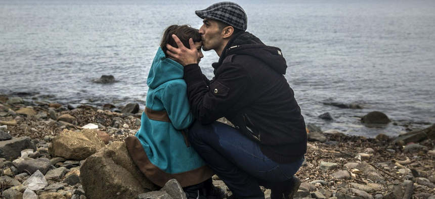 A Syrian man and his daughter reach the beach on the Greek island of Lesbos after crossing the Aegean sea from the Turkish coast in a dinghy.