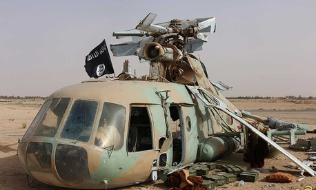 An Islamic State flag sits on a damaged helicopter at Tadmur military airbase in May.
