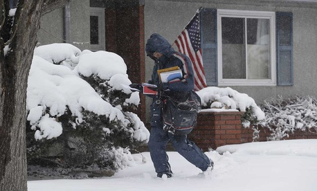 Postal worker Van Nguyen walks through the snow as he delivers the mail in Denver in 2013.
