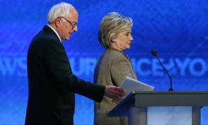 Bernie Sanders, left, and Hillary Clinton return after a break during a Democratic presidential primary debate Saturday, Dec. 19, 2015, at Saint Anselm College in Manchester, N.H.