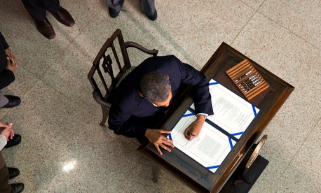 Obama signs a bill in 2014 in the New Executive Office Building.