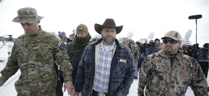 Ammon Bundy, center, one of the sons of Nevada rancher Cliven Bundy, walks off after speaking with reporters during a news conference at Malheur National Wildlife Refuge headquarters Monday.