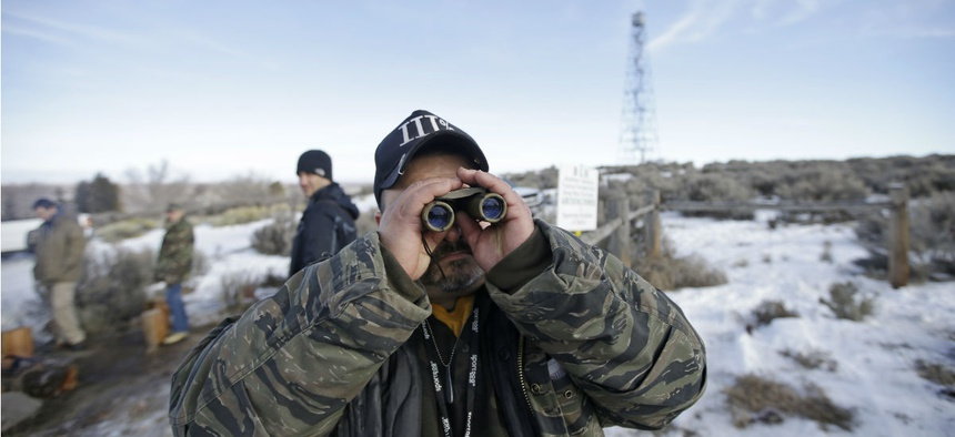 Sean Anderson, of Idaho, a supporter of the group occupying the Malheur National Wildlife Refuge, looks through binoculars at the front gate Jan. 6.