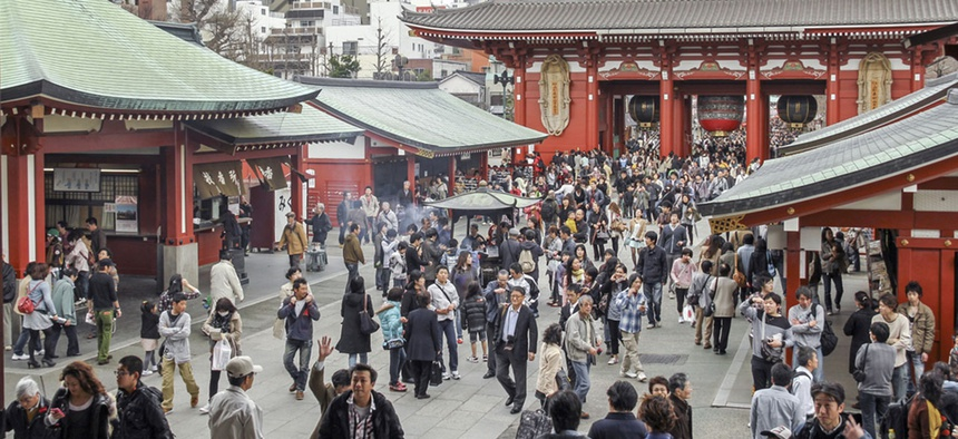 A crowd of Japanese people walk near a Buddhist temple in Tokyo in 2012.