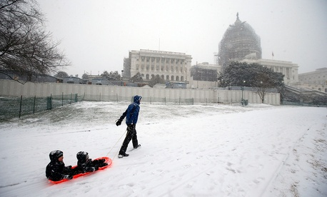 Ben Cichy pulls a sled with his sons Adrian, 18-months-old, and Logan 3, inside as they head for sledding in the snow on Capitol Hill Friday.