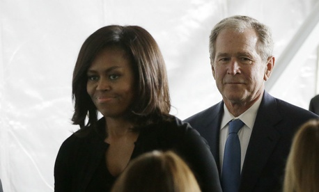 Former president George W. Bush leaves the funeral service of Nancy Reagan, behind First Lady Michelle Obama.