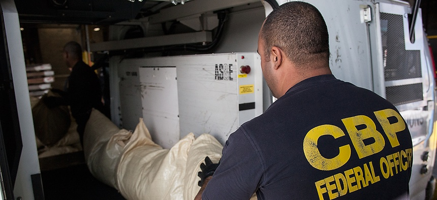 A  Customs and Border Patrol officer lines up bags of spice that will run on a conveyor belt through a mobile x-ray unit in Newark in 2012.