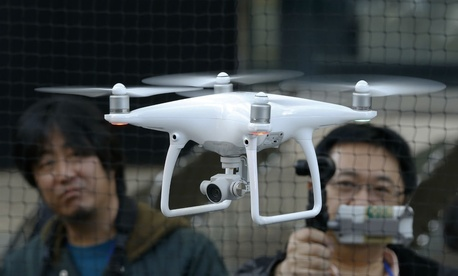 Employees of DJI, a major Chinese consumer-drone maker, demonstrate their latest model Phantom 4 in Tokyo on March 3.