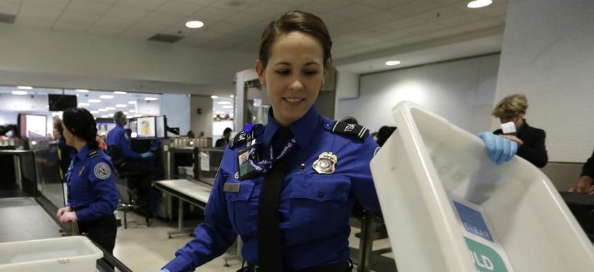 A TSA agent screens passengers' belongings at Miami International Airport in November 2015.